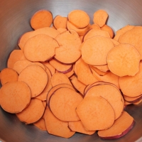 Step 3 - After slicing sweet potatoe,  place in large bowl and toss with oil